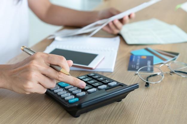 Kobieta trzyma rachunki i używa kalkulatora, konta i oszczędzania pojęcie.