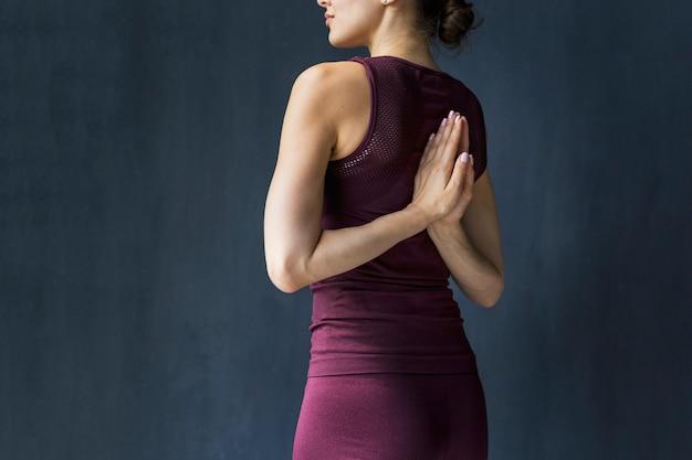 Kobieta trzyma ręce w pozycji modlitwy za jej plecami