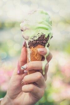 Kobieta trzyma ręcznie lody. rożek do topienia lodów. koncepcja ludzi na świeżym powietrzu jedzenie i deser.