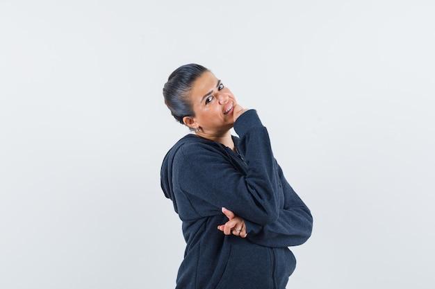 Kobieta trzyma rękę na brodzie w bluzie z kapturem i wygląda wesoło. przedni widok.