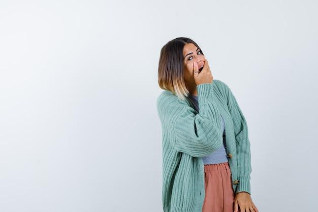 Kobieta trzyma rękę na otwartych ustach w ubranie i wygląda na zaskoczoną. przedni widok.