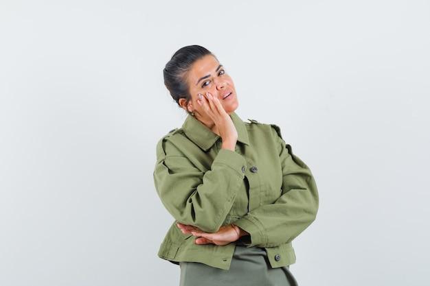 Kobieta trzyma rękę na policzku w kurtce, t-shirt i wygląda pewnie