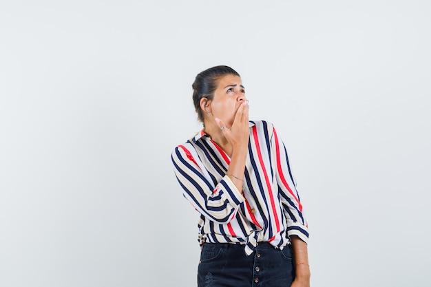 Kobieta trzyma rękę na ustach w koszuli, spódnicy i smutny.