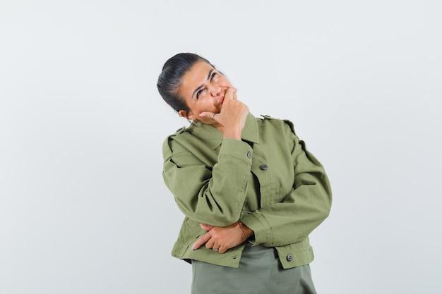 Kobieta trzyma rękę na ustach w kurtce, t-shirt i marzycielski wygląd.