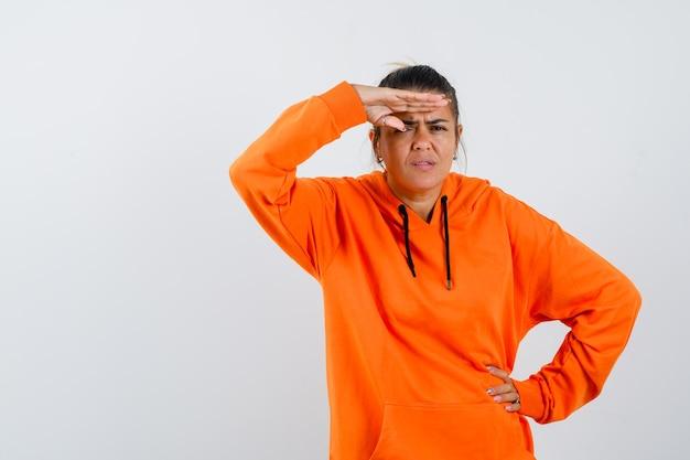 Kobieta trzyma rękę nad głową w pomarańczowej bluzie z kapturem i wygląda ciekawie