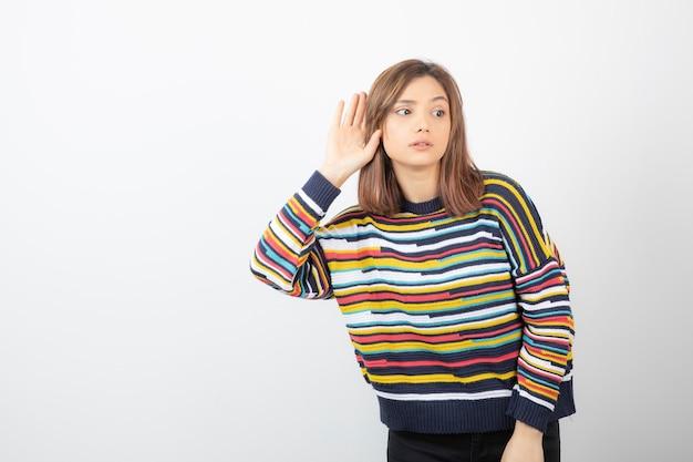 Kobieta trzyma rękę w pobliżu ucha i słucha uważnie na białym tle na tle szaro-białej ściany.