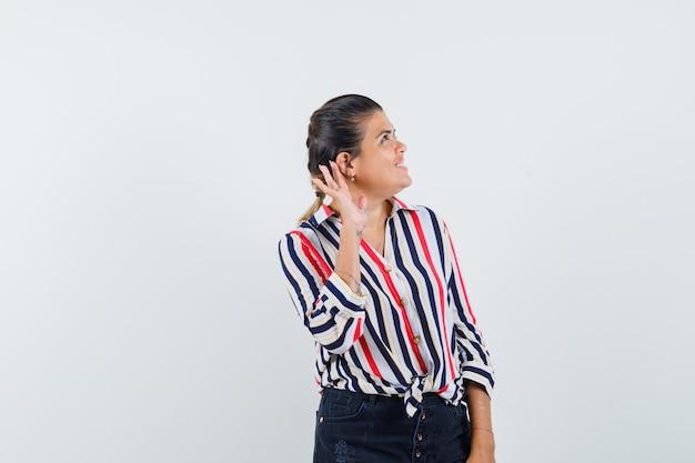 Kobieta trzyma rękę za ucho w koszuli, spódnicy i ciekawi