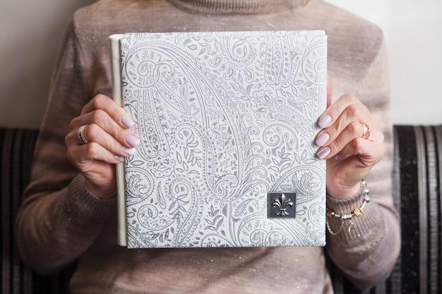Kobieta trzyma rodzinną fotoksiążkę. album fotograficzny ślubny lub rodzinny z okładką z naturalnej skóry. kolor biały z ozdobnym tłoczeniem.