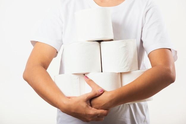 Kobieta trzyma rolki papieru toaletowego