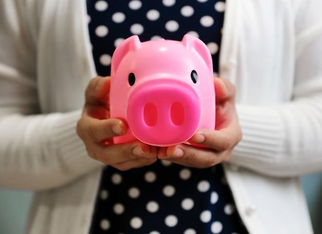 Kobieta trzyma różowy piggy bank.