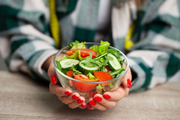 Kobieta trzyma sałatki w jej ręce dla zdrowego stylu życia