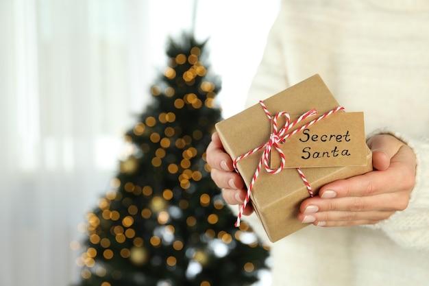 Kobieta trzyma secret santa pudełko, miejsca na tekst.