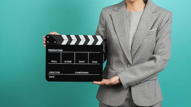 Kobieta trzyma się za ręce czarny klaps lub klapkę filmową i nosi szary garnitur na miętowym zielonym tle