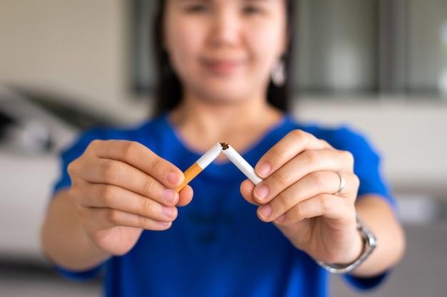 Kobieta trzyma się za ręce i łamie papierosa w celu rzucenia palenia