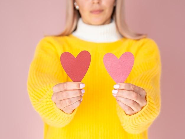 Kobieta trzyma śliczne papierowe serca