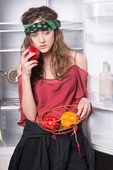 Kobieta trzyma słodką paprykę w lodówce z otwartymi drzwiami na białym tle. zdrowa żywność i koncepcja diety.
