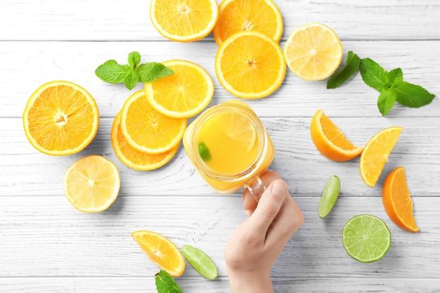 Kobieta trzyma słoik z masonem ze świeżym sokiem pomarańczowym na stole