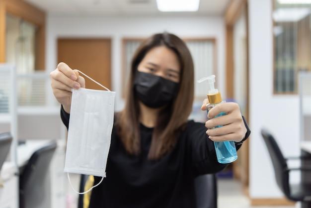 Kobieta trzyma słoik z żelem higienicznym i maskę