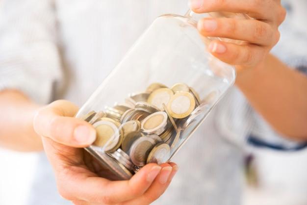 Kobieta trzyma słój z pieniądze