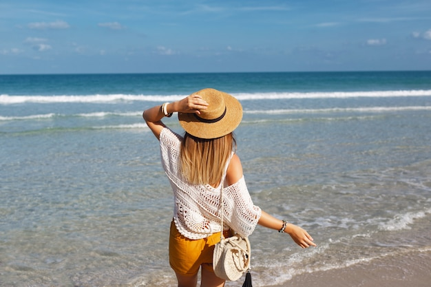 Kobieta trzyma słomianą torbę i odprowadzenie na plaży