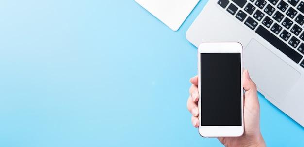 Kobieta trzyma smartfon na białym tle z minimalną niebieską przestrzenią na biurko, leżał na płasko, widok z góry, makieta