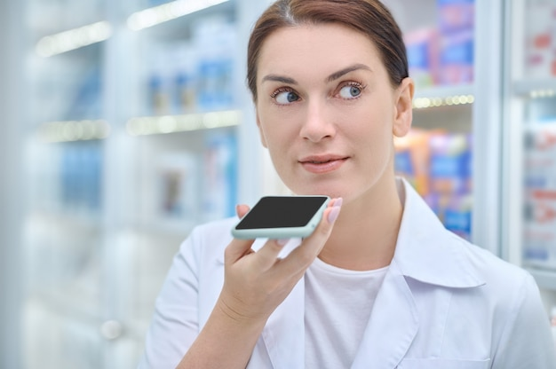 Kobieta trzyma smartfon na poziomie twarzy