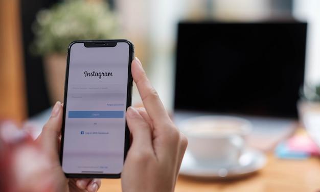 Kobieta trzyma smartfon z aplikacją instagram na ekranie w kawiarni. instagram to aplikacja do udostępniania zdjęć na smartfony.