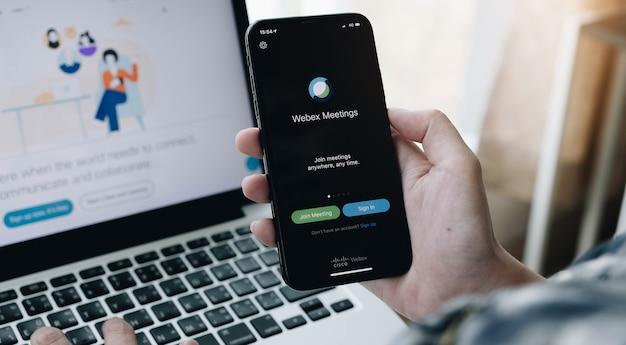Kobieta trzyma smartfon z aplikacją webex spotkać. aplikacja do wideokonferencji, dystansu społecznego i pracy domowej.