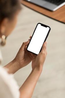 Kobieta trzyma smartfon z bliska