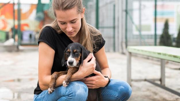 Kobieta trzyma smutnego psa ratunkowego w schronisku adopcyjnym