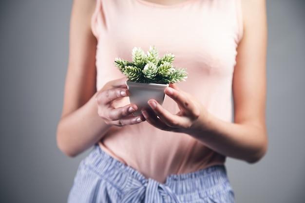 Kobieta trzyma soczysty kwiat na wazonie.
