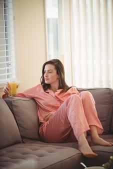 Kobieta trzyma sok siedząc na kanapie