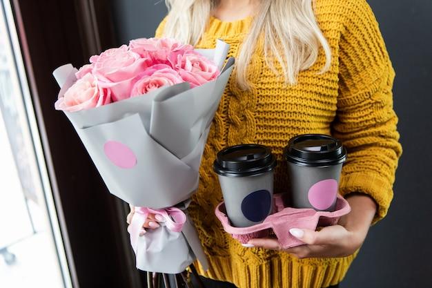 Kobieta trzyma specjalny pojemnik na dwie filiżanki kawy na wynos i bukiet różowych kwiatów.