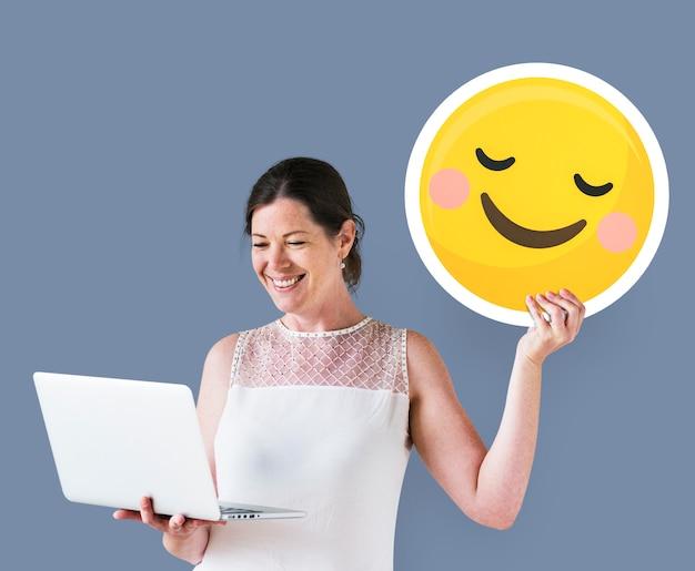 Kobieta trzyma spłonionego emotikona i za pomocą laptopa