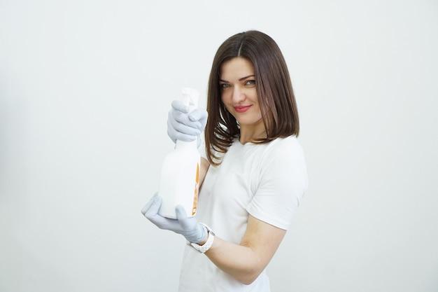 Kobieta trzyma sprayem z antyseptykiem lub detergentem, takim jak pistolety koncepcja zdrowia lub czyszczenia covid na białym tle