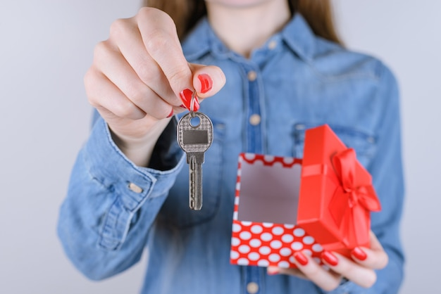 Kobieta trzyma srebrny metalowy klucz i otwiera pudełko