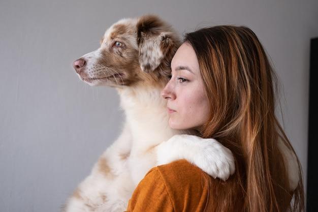 Kobieta trzyma sród małe słodkie owczarek australijski red merle szczeniak. najlepsi przyjaciele. miłość i przyjaźń między człowiekiem a zwierzęciem. patrząc w jednym kierunku.