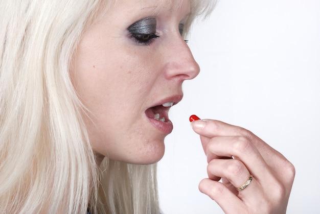 Kobieta trzyma środek przeciwbólowy między palcami