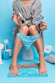 Kobieta trzyma środki przeciwbólowe i tampon cierpi na skurcze miesiączkowe nosi szlafrok koronkowe majtki pozuje w toalecie na niebiesko