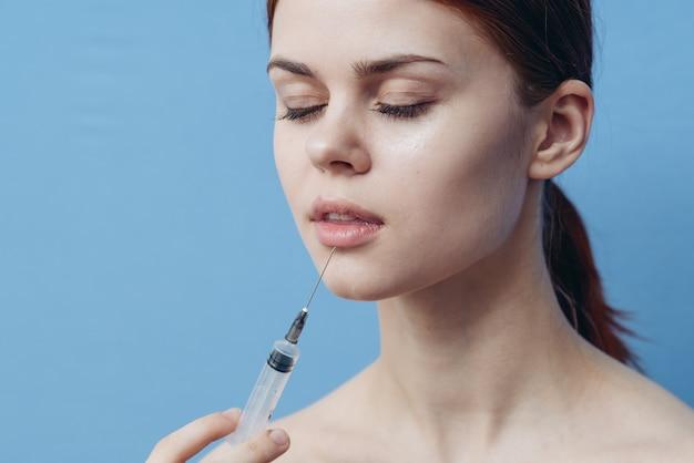Kobieta trzyma strzykawkę w ręku operacja wstrzyknięcia botoksu zmiana wyglądu