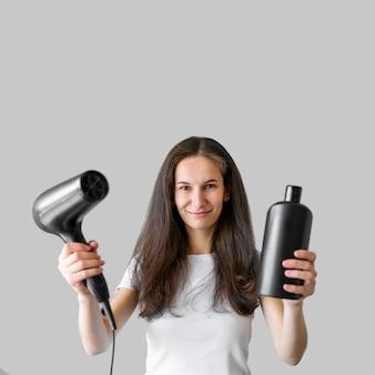 Kobieta trzyma suszarkę do włosów