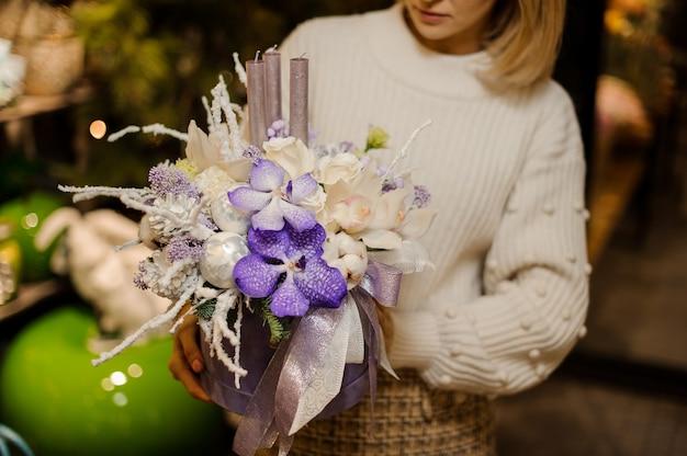 Kobieta trzyma świąteczną kompozycję z fioletowymi i białymi orchideami i różami