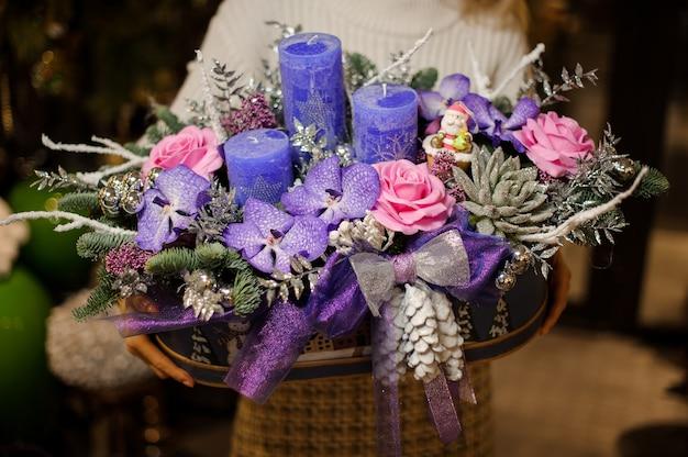 Kobieta trzyma świąteczną kompozycję z fioletowymi i różowymi kwiatami, sukulentami, gałęziami jodły i świecami w pudełku