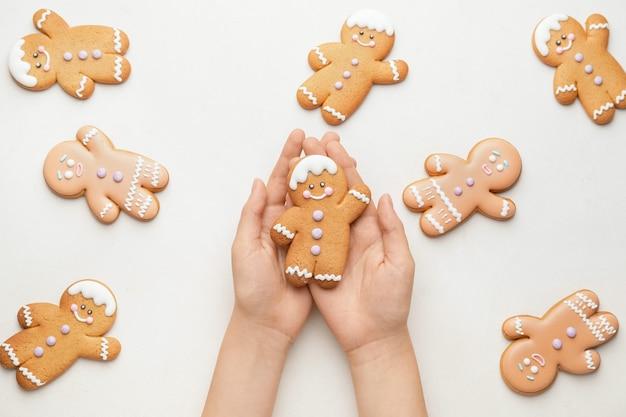 Kobieta trzyma świąteczne ciasteczka na białym tle