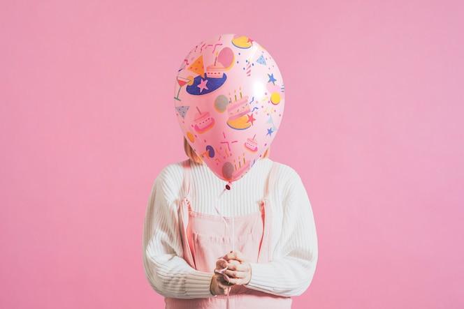 Kobieta trzyma świąteczny balon na prostym różowym tle