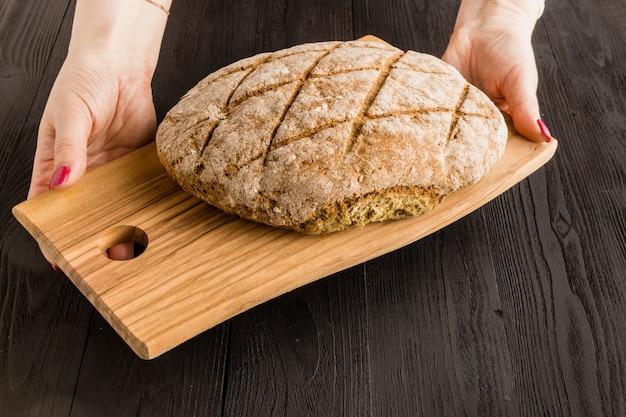 Kobieta trzyma świeży chleb rustykalny