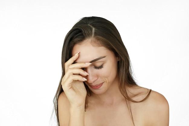 Kobieta trzyma swój plam przed czołem patrzeje haniebnym