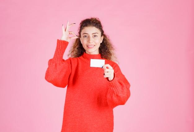 Kobieta trzyma swoją nową wizytówkę i pokazuje znak ręki przyjemności.