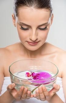 Kobieta trzyma szklaną miskę z wodą i kwiaty orchidei.