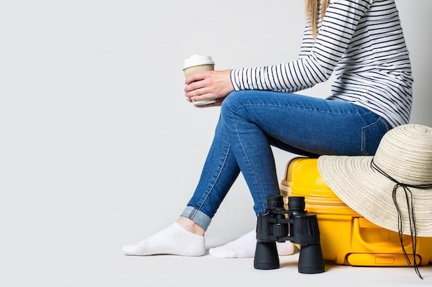 Kobieta trzyma szklankę kawy i siedzi na żółtej plastikowej walizce z letnim kapeluszem przeciwsłonecznym i lornetką na jasnej przestrzeni.